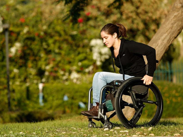 A woman riding her wheelchair with SoftWheel wheels