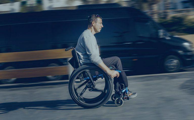 A man riding his wheelchair with SoftWheel wheels